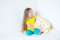 Прелестная маленькая девочка играя с подушкой на кровати в ее спальне Стоковые Изображения RF