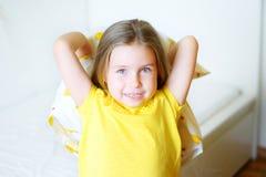 Прелестная маленькая девочка играя с подушкой на кровати в ее спальне Стоковая Фотография