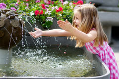 Прелестная маленькая девочка играя с фонтаном города на горячем и солнце Стоковые Изображения RF