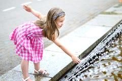 Прелестная маленькая девочка играя с фонтаном города на горячий и солнечный летний день Стоковое фото RF