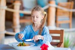 Прелестная маленькая девочка имея обедающий на внешнем кафе Стоковое фото RF
