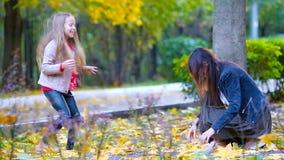 Прелестная маленькая девочка и счастливая мать наслаждаются днем падения в парке осени outdoors Семейный отдых осени сток-видео