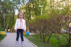 Прелестная маленькая девочка на коньках ролика в парке Стоковое фото RF