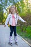 Прелестная маленькая девочка на коньках ролика в парке Стоковая Фотография