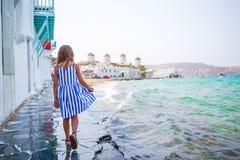 Прелестная маленькая девочка на меньшей Венеции самая популярная туристическая зона на острове Mykonos, Греции Красивая улыбка ре Стоковая Фотография RF