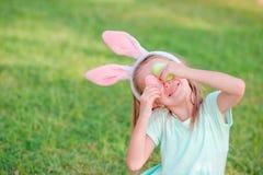 Прелестная маленькая девочка на празднике пасхи сидя на траве Стоковые Фотографии RF