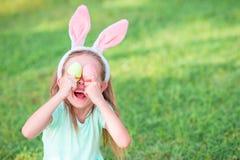 Прелестная маленькая девочка на празднике пасхи сидя на траве Стоковая Фотография RF