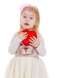 Прелестная маленькая девочка обнятая к его коробке комода внутри Стоковое Фото
