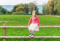 Прелестная маленькая девочка отдыхая на загородке Стоковая Фотография