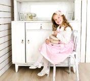Прелестная маленькая девочка сидя на стуле с подарочной коробкой Стоковые Фото