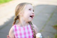 Прелестная маленькая девочка смеясь над с мороженым на лете Стоковые Фото