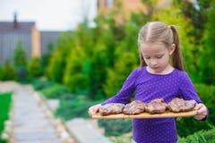 Прелестная маленькая девочка с зажаренными стейками в руках внешних Стоковые Фото
