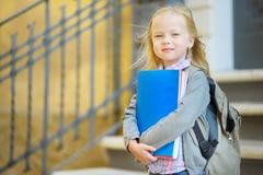 Прелестная маленькая школьница изучая outdoors на яркий день осени Молодой студент делая ее домашнюю работу Образование для малых Стоковое Изображение