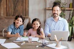 Прелестная семья родитель-одиночки сидя на таблице Стоковые Изображения