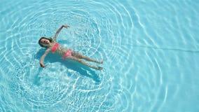 Прелестная счастливая маленькая девочка наслаждается поплавать в бассейне Летние каникулы семьи, ребенк ослабляют на бассейне сток-видео