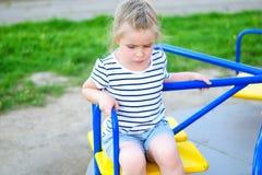 Прелестная унылая маленькая девочка на carousel Стоковое Фото