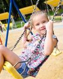 Прелестная усмехаясь маленькая девочка имея потеху на качании Стоковые Изображения