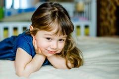 Прелестная усмехаясь маленькая девочка проспала вверх в ее кровати стоковая фотография rf