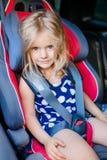 Прелестная усмехаясь маленькая девочка с длинными светлыми волосами buckled в автомобиле Стоковое фото RF