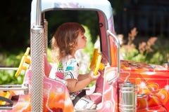 Прелестное катание девушки малыша на автомобиле в парке атракционов Стоковые Изображения RF