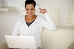 Прелестно женщина с нот наушников слушая Стоковая Фотография