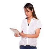 Прелестно чтение молодой женщины на экране ПК таблетки Стоковые Изображения