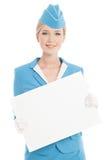 Прелестно Stewardess в голубой форме с чистым бланком на белизне стоковая фотография rf