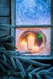 Прелестные горящие свечи для рождества в замороженном окне Стоковая Фотография