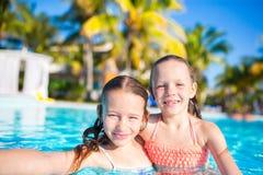 Прелестные маленькие девочки играя в открытом бассейне Милое selfie взятия детей Стоковые Изображения