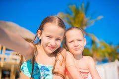 Прелестные маленькие девочки играя в открытом бассейне Милое selfie взятия детей Стоковые Фото