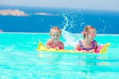 Прелестные маленькие девочки играя в открытом бассейне с красивым видом Стоковое фото RF