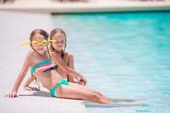 Прелестные маленькие девочки играя в открытом бассейне Стоковая Фотография RF
