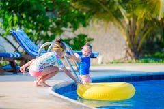 Прелестные маленькие девочки играя в открытом бассейне Стоковые Изображения RF