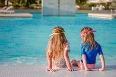 Прелестные маленькие девочки играя в открытом бассейне Стоковое Изображение