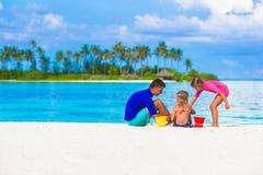 Прелестные маленькие девочки и папа играя с пляжем Стоковое фото RF