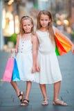 Прелестные маленькие девочки на покупках Портрет детей с хозяйственными сумками в малом итальянском городке стоковое фото