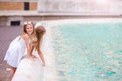 Прелестные маленькие девочки около фонтана Trevi в Риме Счастливые дети наслаждаются их европейскими каникулами в Италии Стоковые Фото