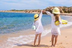 Прелестные милые девушки имеют потеху на белом пляже во время Стоковое Изображение