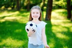 Прелестный маленький поклонник футбола веселя на горячий летний день на парке Стоковые Изображения RF