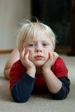 Прелестный маленький ребенок кладя на пол живущей комнаты стоковое изображение
