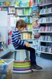Прелестный маленький ребенок, мальчик, сидя в книжном магазине стоковое изображение