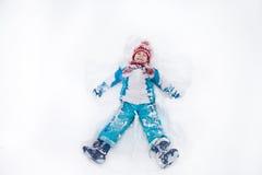 Прелестный мальчик в синем пиджаке, красной шляпе и шарфе, лежа дальше Стоковое Фото