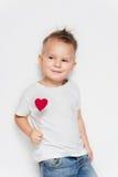 Прелестный мальчик представляя с валентинкой формы сердца стоковое изображение rf