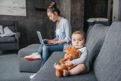 Прелестный мальчик при игрушка плюшевого медвежонка сидя на кресле пока его мать работая на компьтер-книжке дома Стоковое Изображение
