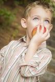 Прелестный мальчик ребенка есть красное Яблоко снаружи Стоковые Фотографии RF
