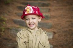 Прелестный мальчик ребенка при шляпа пожарного играя снаружи Стоковое Фото