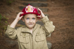 Прелестный мальчик ребенка при шляпа пожарного играя снаружи Стоковое Изображение