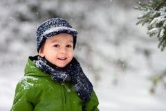 Прелестный мальчик, дуя снежинки снаружи в снежном дне стоковые фото
