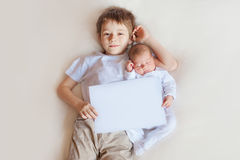 Прелестный младенец и более старый брат на белой предпосылке скопируйте космос Стоковая Фотография RF