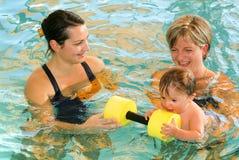 Прелестный младенец наслаждаясь плавать в бассейне с его матерью стоковая фотография